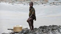 Boy with a fishing net standing on the oil stained bank of a creek in Nigeria (Photo: EPA/MARTEN VAN DIJL)